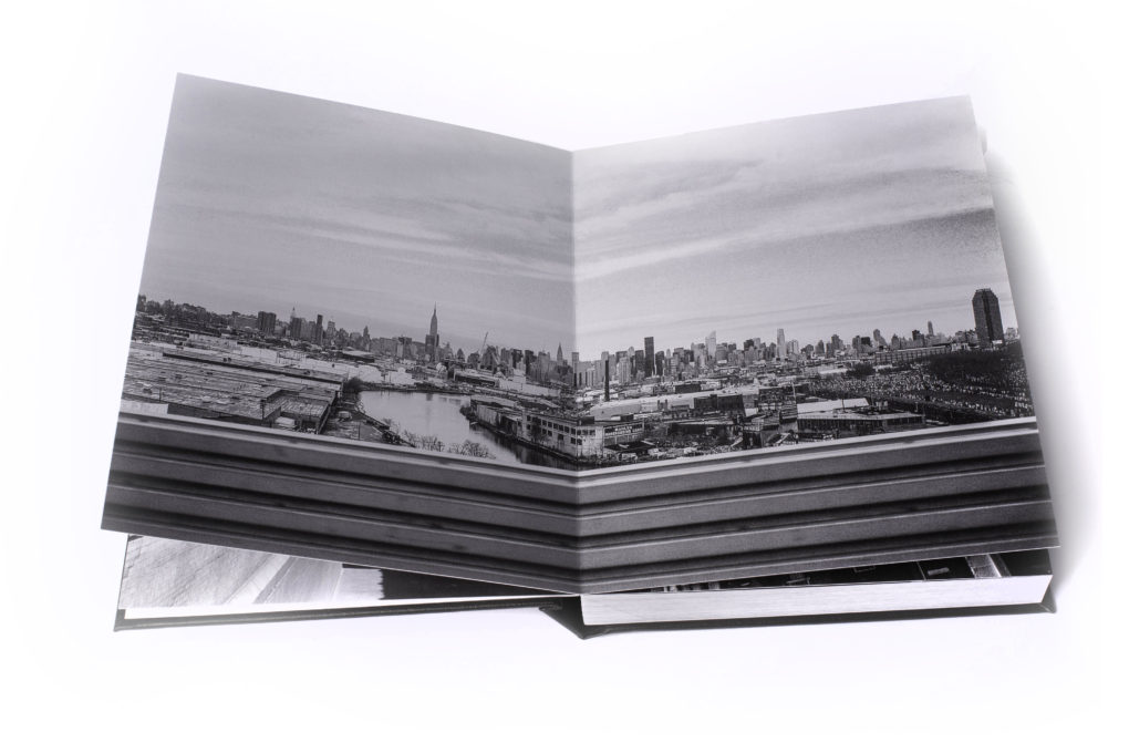 Image of a two page full bleed image of the New York skyline that is bound in a leather book.